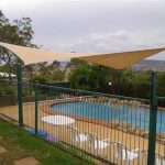 Cream shade sail over pool