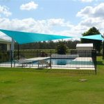 Green shade sail over pool