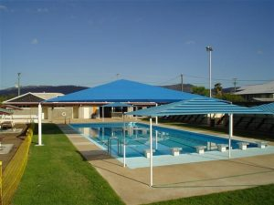 Blue striped shade structure over pool
